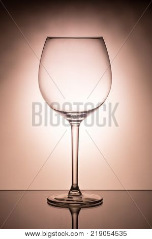 One empty wineglass for red wine on diffusion lit background, advertizing shot for restaurant, winemaking