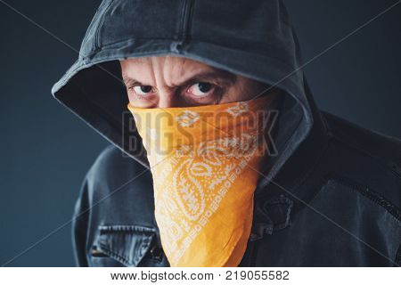 Hooded gang member criminal with scarf over face looking at camera