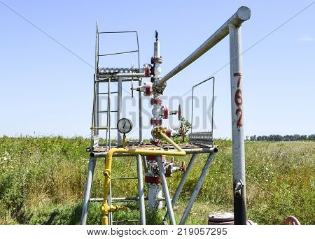 Well for oil and gas production. Oil well wellhead equipment. Oil production.