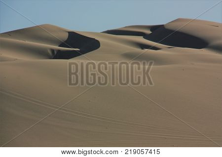 Oasis In Desert In Peru With Palm Trees And Dunes