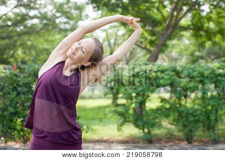 Closeup portrait of content young attractive woman wearing sportswear, raising clasped hands and stretching body in park with green view in background. Front view.