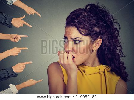Anxious woman judged by different people fingers pointed at her. Concept of accusation of guilty girl. Negative human emotions face expression feeling
