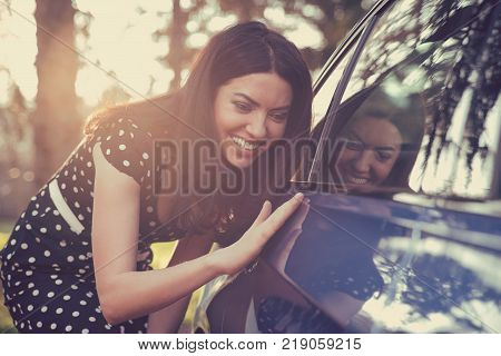 Excited young woman and her new car outdoors with sunlit forest in background.
