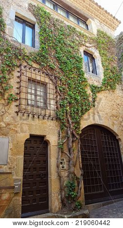 PALS, SPAIN - MAY 14, 2017: Facade of a house in a small medieval village of Catalonia