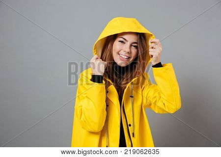 Portrait of a happy girl dressed in raincoat posing with hood on her head isolated over gray background