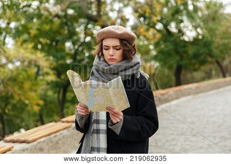 Portrait of a concentrated girl dressed in autumn clothes holding city guide map while walking outdoors
