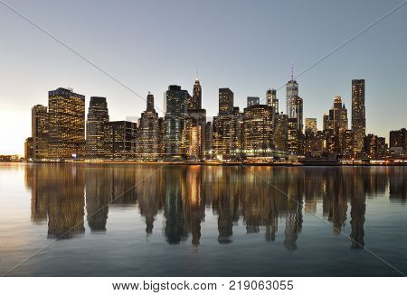 Manhattan skyline reflected in the water of the East River.