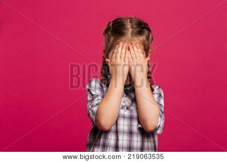 Image of little girl child standing isolated over pink background covering face with hands.