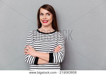 Portrait of a smiling woman standing with arms folded and looking away isolated over gray background