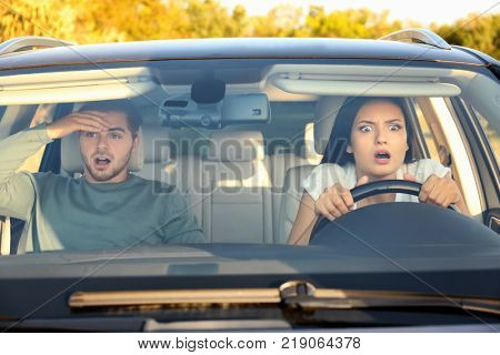 Emotional young couple in car during auto accident
