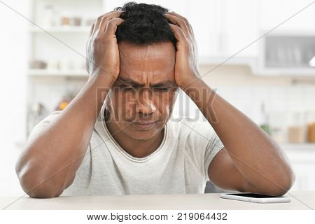 Troubled mature African-American man at home