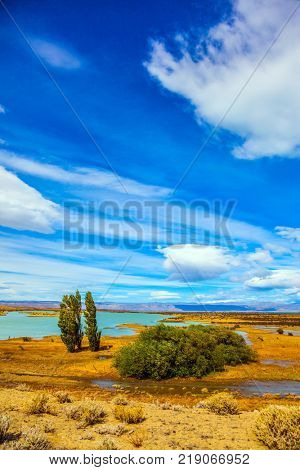 The concept of active and exotic tourism. Flat plain with shallow lakes and yellowed grass. Patagonian Pampas. Strong wind carries clouds