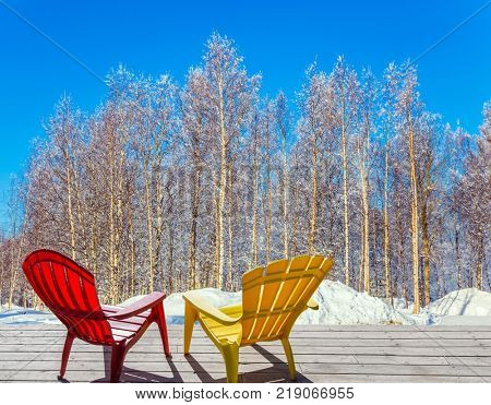 Bright winter frosty day in the Arctic. Comfortable red and yellow plastic chaise lounges for relaxing in forest. The concept of extreme and ecotourism tourism