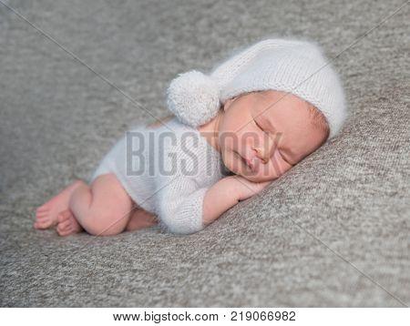 Newborn boy sleeping in funny bonnet