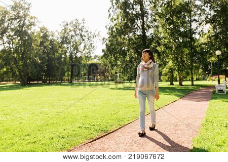 pregnancy, people and motherhood concept - happy pregnant asian woman walking at park