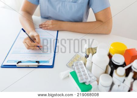 medicine, healthcare and people concept - nurse or doctor with drugs and clipboard writing prescription or medical report at hospital