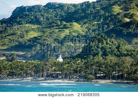 Beautiful beach with palm trees and mountains in Dominican Republic.