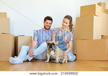 mortgage, people and real estate concept - happy couple with boxes and french bulldog dog moving to new home