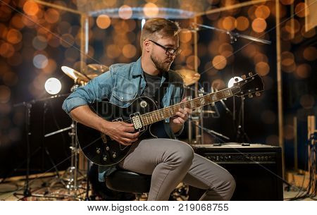 music, people, musical instruments and entertainment concept - male guitarist playing electric guitar at studio or concert over holidays lights background