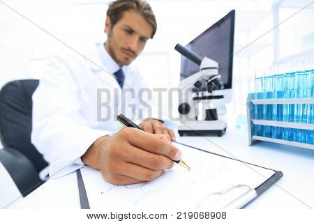 scientist makes a note of experiment in the laboratory