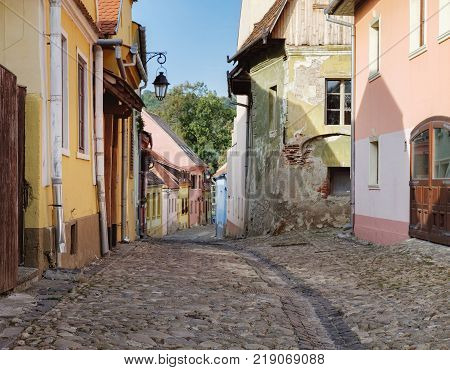 Sighisoara, Romania - September 28, 2017: Cobbled street with medieval houses in the historic center of Sighisoara, Romania