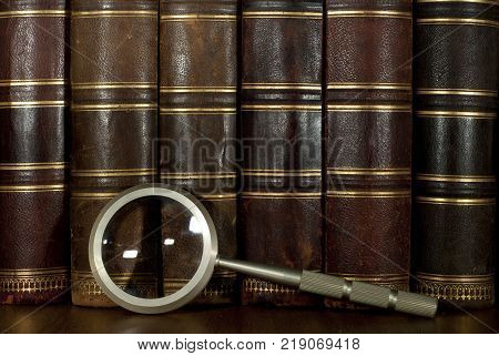 background: a row of worn leather antiquarian book spines with gold embossing and a magnifying glass