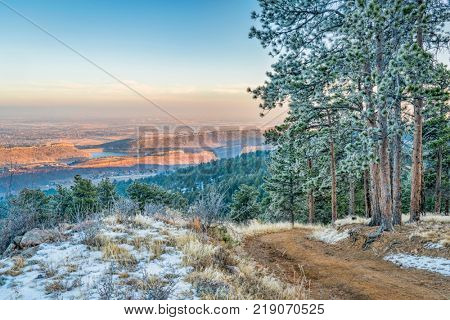 unset view of plains, foothills and lake in northern Colorado, a view from  Towers Trail in Horsetooth Mountain Park with pine trees covered by frost