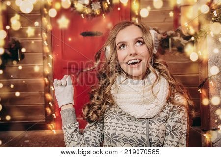Happy pretty girl in winter clothes is sitting on the porch of a house decorated for Christmas and holding a cup of tea. Time for miracles.
