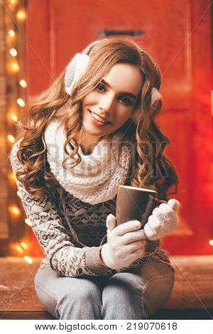 Pretty girl in winter clothes is sitting on the porch of a house decorated for Christmas and holding a cup of tea. Time for miracles.