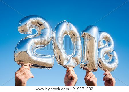 men hands holding some silvery number-shaped balloons forming the number 2018, as the new year, against the blue sky