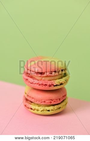 a pile of delicious pink and green macarons of mixed flavors on a pink and green background with a blank space on top