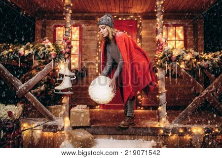 Happy girl in a warm winter clothes and blanket holds a big snowball in her hands near the house decorated for Christmas. Time for miracles. Merry Christmas and Happy New Year.