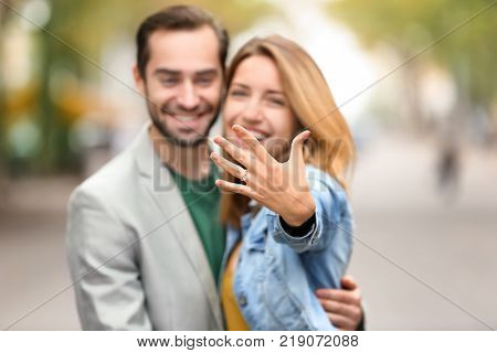 Young man with his beloved showing engagement ring outdoors