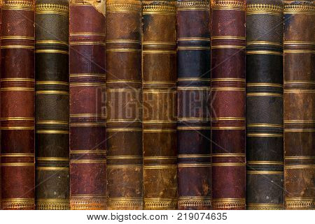 background: a row of worn leather antiquarian book spines with gold embossing