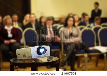 Projector on background of blur sitting people on yellow-blue chairs in bright conference hall