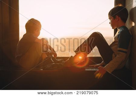 two boys looking out the window at sunset. the children sitting on the windowsill. Copy space for your text