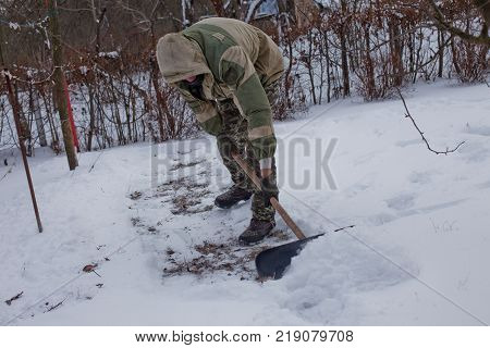 man clears the yard of the snow With Shovel. Heavy snowfall in winter. High level of snow. Snowy snowdrift.