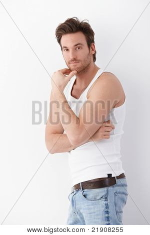 Athletic young man standing at wall, wearing undershirt and jeans.?