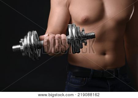 Muscular young bodybuilder with dumb-bell on dark background