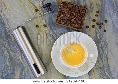Cup of hot coffee with hand coffee grinder to grind beans. Top view of mini grinding made of steel with handle to make freshly ground coffee drink on stone background