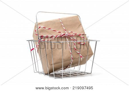 Gift package wrapped in brown paper in basket on white background.