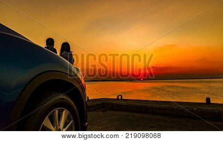 Silhouette of happiness couple standing and relaxing on the beach in front of the car with orange and blue sky at sunset. Summer vacation and travel concept. Romantic young couple dating at seaside.