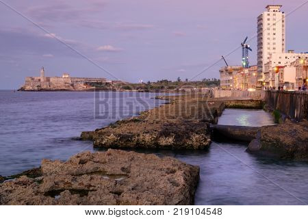 The Malecon seawall and El Morro castle in Havana at sunset