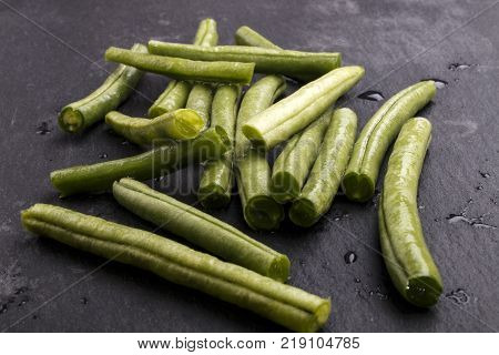 wet and clean green beans with water drops on slate