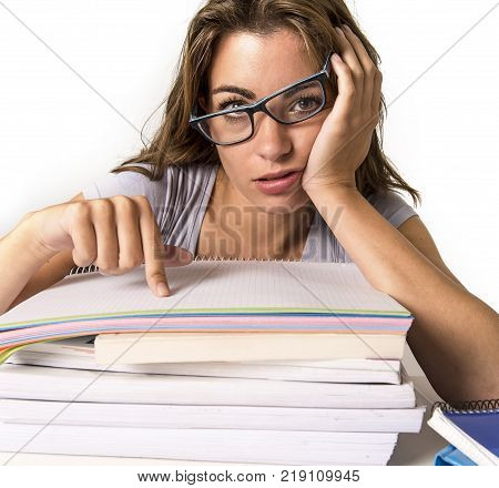 young attractive and beautiful tired student girl leaning on school books pile tired and exhausted after studying preparing exam looking wasted taking a nap in stress education concept