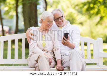 old age, technology and people concept - happy senior couple with smartphone at summer park