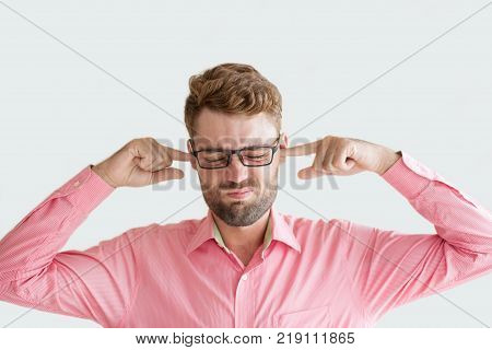 Portrait of annoyed handsome young man stopping his ears with fingers. Businessman getting too much news and feeling high stress. Stressful job and stopping ears concept