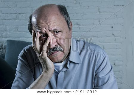 head portrait of senior mature old man on his 70s looking sad and worried suffering pain and depression in sadness face expression isolated in retirement and Alzheimer disease concept