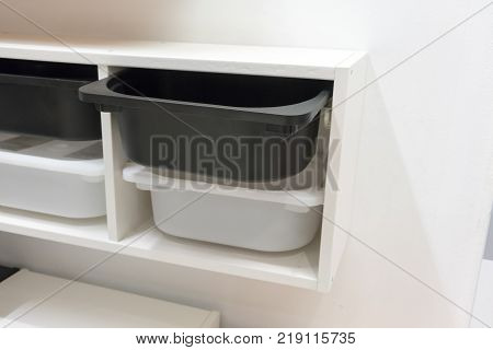 black and white plastic storage drawer in white cabinet for room organizer isolated on white background