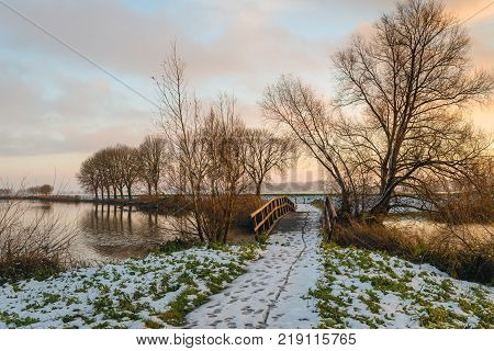 Idyllic landscape with a wooden footbridge in wintertime during sunset.